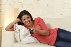 Attractive latin woman at home sofa couch laughing and smiling happy watching television. Young beautiful and attractive latin woman at home sofa couch laughing Stock Photo