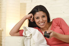 Attractive latin woman at home sofa couch laughing and smiling happy watching television. Young beautiful and attractive latin woman at home sofa couch laughing Stock Image