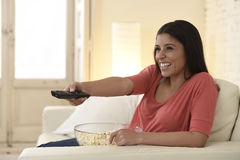 Attractive latin woman at home sofa couch laughing and smiling happy watching television Stock Images