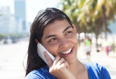 Attractive latin woman with long dark hair at phone in city Stock Images