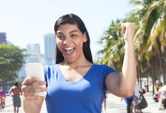 Attractive latin woman receiving good news on cellphone Stock Photo