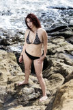 Attractive Latina Woman Standing In Bikini On Rocks With Ocean Stock Photography