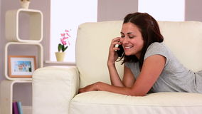 Attractive laughing brunette lying on couch phoning stock footage