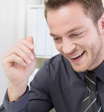 Attractive laughing businessman at office Stock Photo