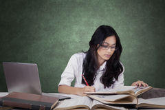 Attractive learner writing on the book in class Royalty Free Stock Photography