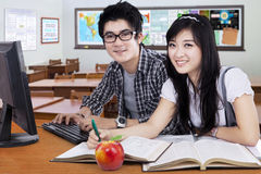Attractive learners smiling at the camera Royalty Free Stock Photos