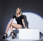 Attractive leggy blonde posing in spotlight. Close-up Royalty Free Stock Photo
