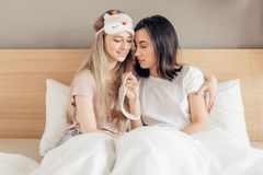 Attractive lesbians girls with sleeping masks preparing to go to bed. Close up photo.it`s high time to sleep royalty free stock images