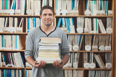 Attractive librarian holding a pile of books standing in library Stock Image