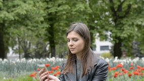 Attractive girl writes sms in the park. Attractive lifestyle girl writes sms in the park stock footage