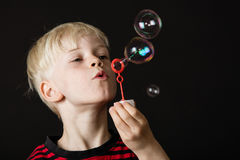 Attractive little blond boy blowing bubbles stock photos