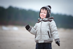 Attractive little boy having fun on winter beach Royalty Free Stock Photography