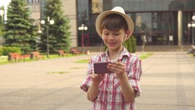 Little boy listens to music on his smartphone. Attractive little boy listening to music on his smartphone outdoors. Handsome male kid in hat holding cellphone in stock images