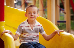 Attractive little boy on a slide in a playground Royalty Free Stock Image