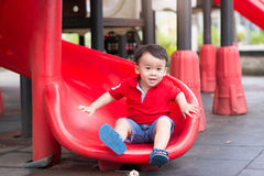 Attractive little boy on a slide in a playground Royalty Free Stock Images