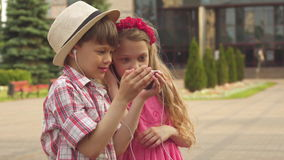 Little children watch something on smartphone outdoors. Attractive little children watching something on smartphone outdoors. Two nice caucasian kids sharing stock video footage