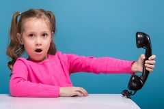 Attractive Little Cute Girl In Pink Shirt With Monkey And Blue Trousers Hold Empty Poster And Talks A Phone Stock Photos