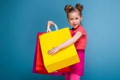 Attractive little cute girl in pink dress holds purple paper bag Stock Photography