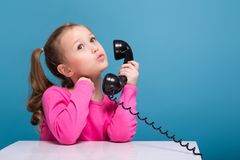 Attractive little cute girl in pink shirt with monkey and blue trousers hold empty poster and talks a phone. Isolated on blue, cute little caucasian brunette Royalty Free Stock Image