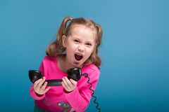 Attractive little cute girl in pink shirt with monkey and blue trousers talks a phone. Isolated on blue, cute little caucasian brunette girl in pink shirt with Royalty Free Stock Photo
