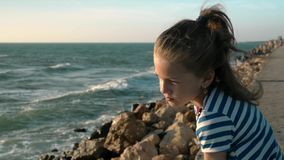 Little girl on the beach. windy day at sunset. Concept loneliness. Attractive little girl on the beach. windy day at sunset. Concept loneliness stock video