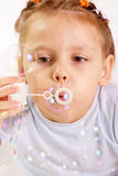 Attractive little girl blowing soap bubbles Royalty Free Stock Photo