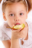 Attractive little girl eating pear Stock Image