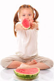 Attractive little girl gives a piece of watermelon Royalty Free Stock Image
