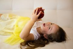 Attractive little girl is holding a red apple in her hand royalty free stock photos