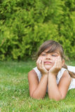 Attractive little girl lying on a lawn. Vertically. Stock Photography