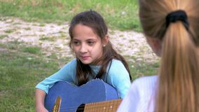 Attractive little girl plays acoustic guitar sings in park while her girlfriend standing listening music performer. Attractive little girl plays acoustic guitar stock video