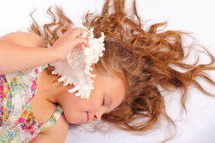 Attractive little girl with seashell Stock Image