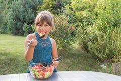 Attractive little girl is tasting fresh vegetable salad outdoor stock image