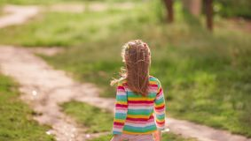 Little girl going away at road royalty free stock image