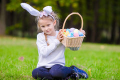 Attractive little girl wearing bunny ears with a basket full of Easter eggs on spring day outdoors Stock Photography