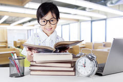 Attractive little learner reading books in class Stock Image