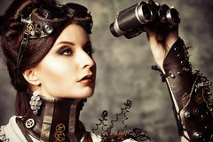 Attractive look. Portrait of a beautiful steampunk woman looking through the binoculars over grunge background Stock Photo