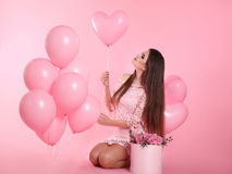 Attractive love brunette woman with balloons and bouquet of rose Stock Image