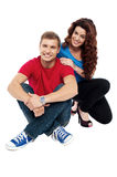 Attractive love couple sitting relaxed on floor Royalty Free Stock Photos