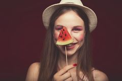 Attractive Lovely girl with pink make up, wearing jeans, hat and top, posing at red studio background, holding slice watermelon. And eat it , emotionally look stock photos