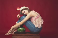 Attractive Lovely girl with pink make up, wearing jeans, hat and top, posing at red studio background sitting on wooden box,. Holding slice watermelon royalty free stock photos