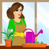 Attractive lovely housewife on the balcony. Holding watering can Royalty Free Stock Images
