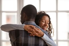 Attractive loving African American girlfriend embrace boyfriend. Standing at home with closed eyes, affectionate couple in love romantic relationship, wife royalty free stock photography