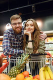 Attractive Loving couple standing near the shopping trolley. With many fruits and looking at the camera Royalty Free Stock Photography