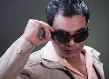 Attractive macho man. Lifting up his sunglasses Royalty Free Stock Photo