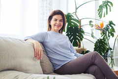 Attractive madam sitting on sofa in bright living room Royalty Free Stock Images