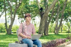 Attractive male asian student is using computer in university`s. Park Royalty Free Stock Photography