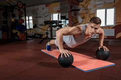 Attractive male athlete performing push-ups on medicine ball Royalty Free Stock Photo