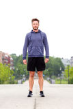 Attractive male athlete standing in middle of street royalty free stock photography