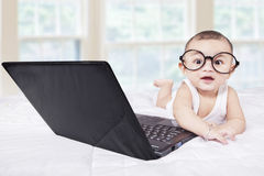 Attractive male baby with laptop on bed Royalty Free Stock Images